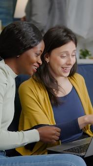 Zwei multiethnische frauen sitzen auf der couch und schauen sich comedy-serien auf einem laptop an, die zusammen rumhängen...