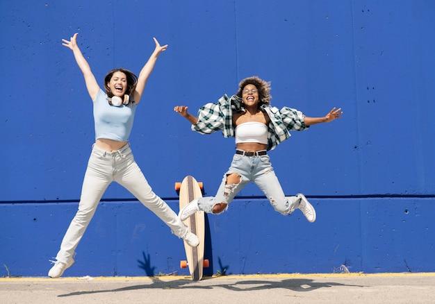 Zwei multiethnische frauen springen auf eine blaue wand, mit skateboard und freizeitkleidung