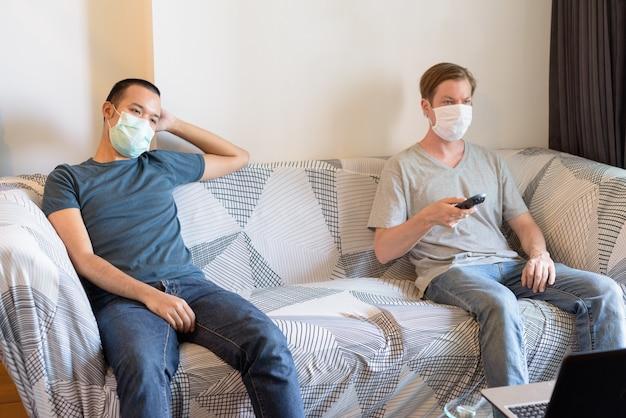 Zwei multiethnische männer mit maske als freunde, die zu hause in quarantäne fernsehen