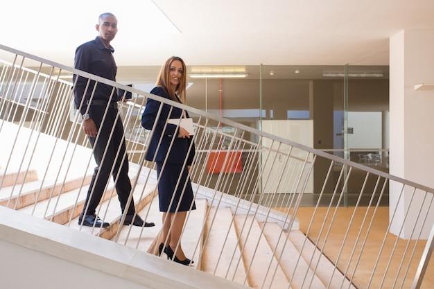Zwei multiethnische mitarbeiter, die auf ihrem weg vom büro aufwerfen