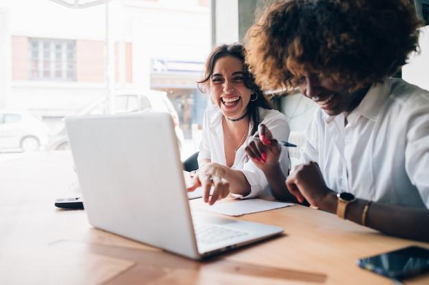 Zwei multikulturelle junge frauen, die spaß beim aufpassen des computers haben