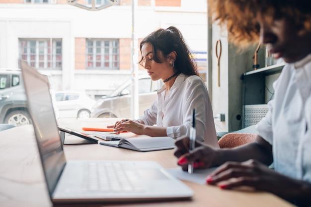 Zwei multikulturelle studenten, die für geschäftsprojekt in einem modernen büro arbeiten