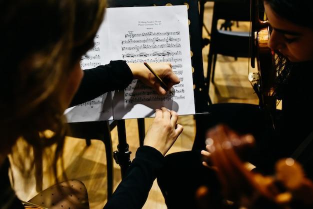 Zwei musikerinnen, die eine partitur mit einem bleistift korrigieren, bevor das orchester zu spielen beginnt.