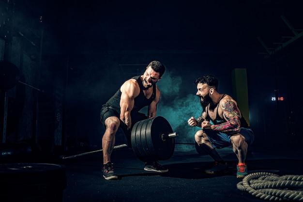 Zwei muskulöse bärtige tätowierte athleten, die an der turnhalle ausbilden