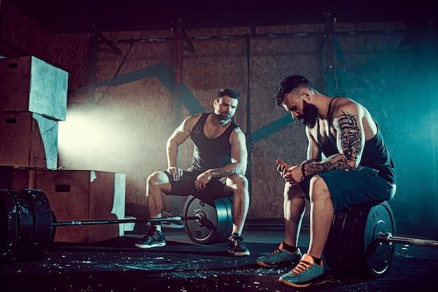 Zwei muskulöse bärtige tätowierte athleten entspannen sich nach dem training und heben schweres gewicht