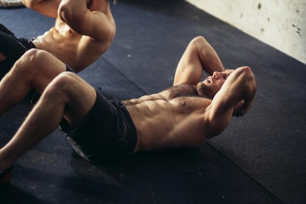 Zwei muskulöse männer, die beim sitzen trainieren