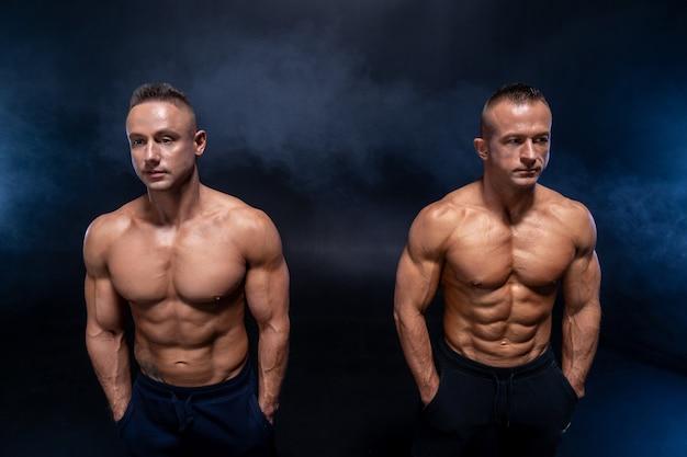 Zwei muskulöse mann isoliert auf dem schwarzen hintergrund starken männlichen nackten oberkörper abs