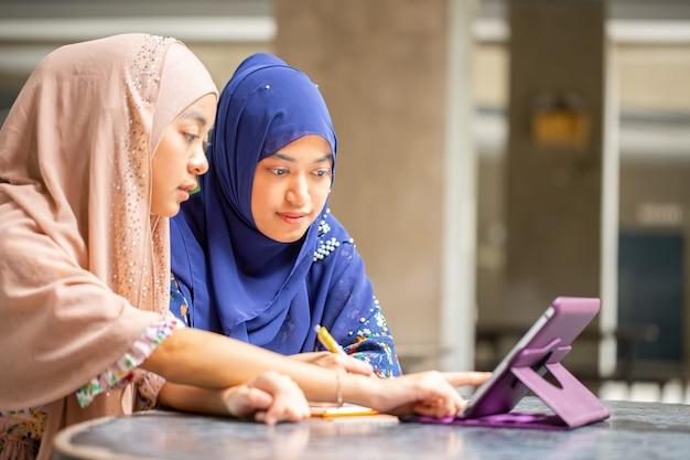 Zwei muslimisch aussehende tablette für das studium an der universität