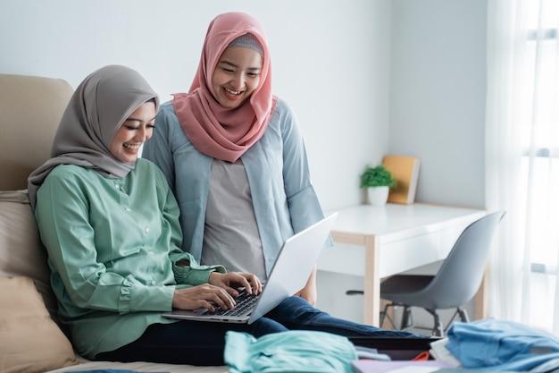 Zwei muslimische frau, die laptop verwendet, um abflugpläne über online-bewerbung zu suchen