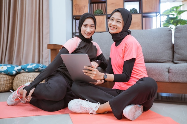 Zwei muslimische frauen, die hijab-sportbekleidung tragen, lächeln, während sie sich auf dem boden entspannen, während sie zu hause ein digitales tablet verwenden