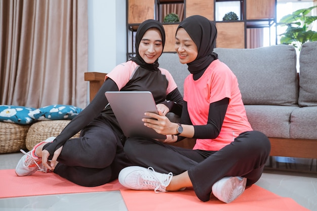 Zwei muslimische frauen, die hijab-sportbekleidung tragen, sitzen auf dem boden, während sie zu hause ein digitales tablet benutzen