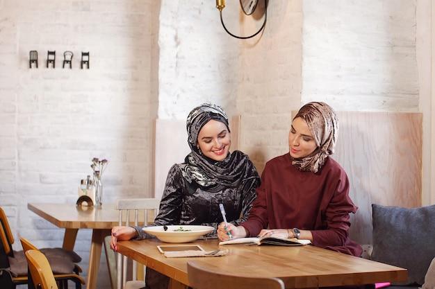 Zwei muslimische geschäftsfrauen trafen sich im café und diskutierten über arbeitsmomente, in denen sie alles in ein notizbuch schrieben