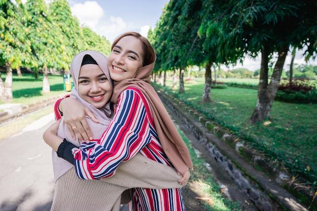 Zwei muslimische mädchen umarmen sich auf dem bürgersteig. fühle dich fröhlich und glücklich zusammen.
