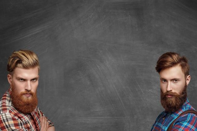 Zwei mutige brutale hipster-männer mit stilvollen bärten in karierten hemden posieren isoliert in den unteren rechten und linken ecken auf einer leeren tafel mit schwerem wütendem ausdruck