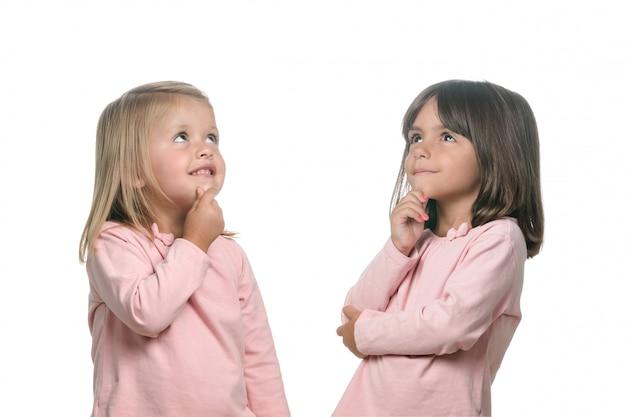 Zwei nachdenkliche kleine mädchen, die an etwas denken