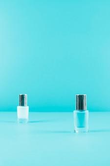 Zwei nagellackflaschen auf blauem hintergrund mit kopienraum für das schreiben des textes