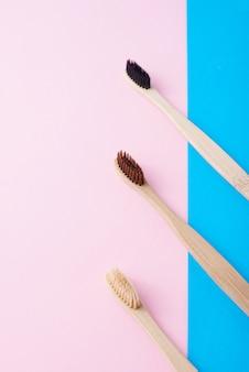 Zwei natürliche hölzerne zahnbürsten auf einem blauen und rosa farbhintergrund
