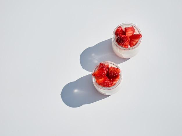 Zwei natürliche joghurts mit frischen erdbeeren lokalisiert auf weiß