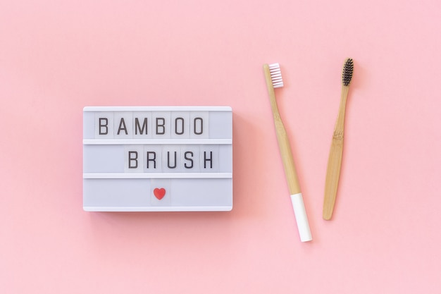 Zwei natürliche umweltfreundliche bambuspinsel und lightbox text bambuspinsel auf rosa