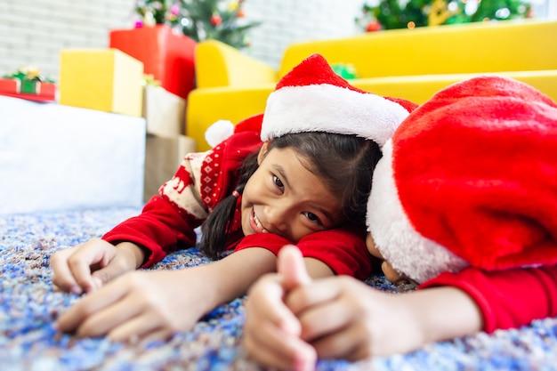 Zwei nette asiatische kindermädchen, die auf dem boden niederlegen und zusammen in der weihnachtsfeier spielen