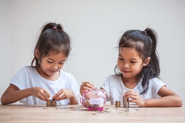 Zwei nette asiatische kindermädchen, die geld in sparschwein stecken, um geld während der zukunft zusammen zu sparen