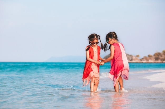 Zwei nette asiatische kindermädchen, die hand halten und zusammen auf strand spielen