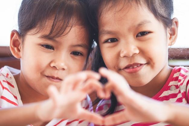 Zwei nette asiatische kindermädchen, die herzform mit den händen zusammen mit liebe bilden