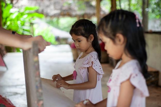Zwei nette asiatische kindermädchen, die lernen, wie man recyclingpapier vom poop der elefanten herstellt