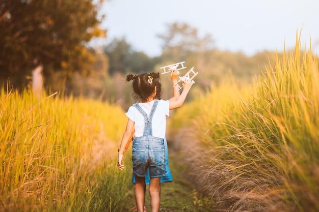 Zwei nette asiatische kindermädchen, die mit hölzernem flugzeug des spielzeugs auf dem gebiet laufen und spielen