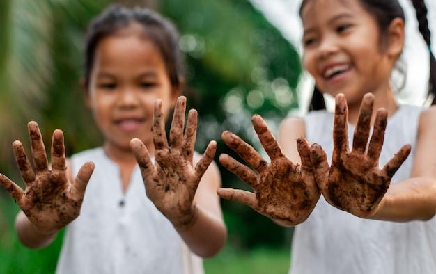 Zwei nette asiatische kindermädchen, die schmutzige hände zeigen, nachdem der baum zusammen im garten gepflanzt worden ist