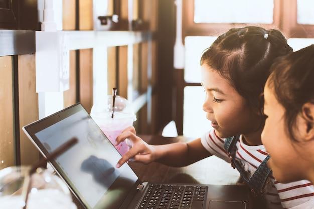Zwei nette asiatische kindermädchen, die zusammen auf laptop im café verwenden und spielen