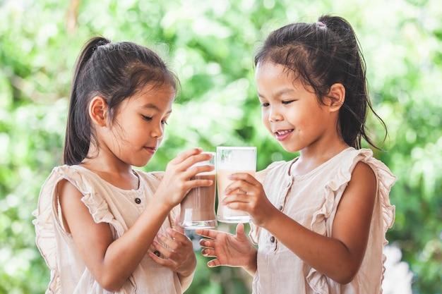 Zwei nette asiatische kindermädchen, die zusammen eine milch vom glas trinken