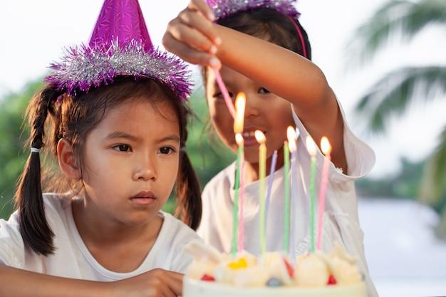Zwei nette asiatische kindermädchen, die zusammen kerze auf geburtstagskuchen in der geburtstagsfeier anzünden