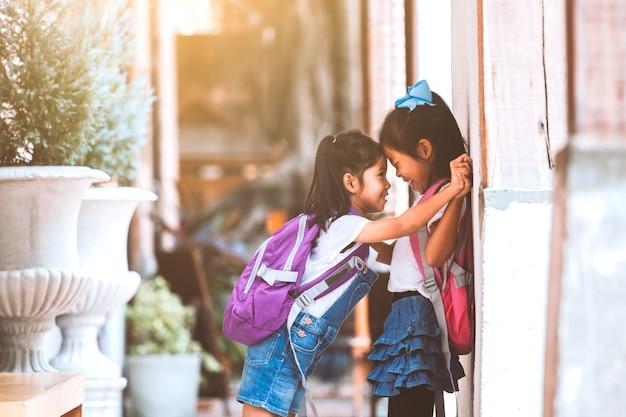Zwei nette asiatische kindermädchen mit der schultasche, die zusammen nach der schule in der schule spielt