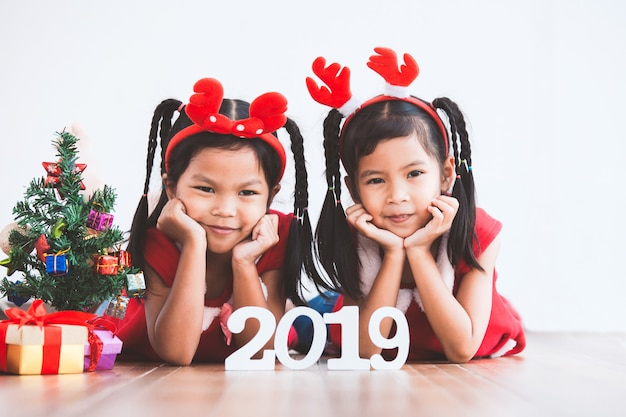 Zwei nette asiatische kindermädchen mit geschenkboxen und weihnachtsbaum, zum von weihnachten zu feiern