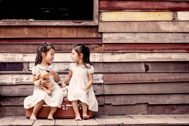 Zwei nette asiatische kleine mädchen, die mit teddybären spielen.