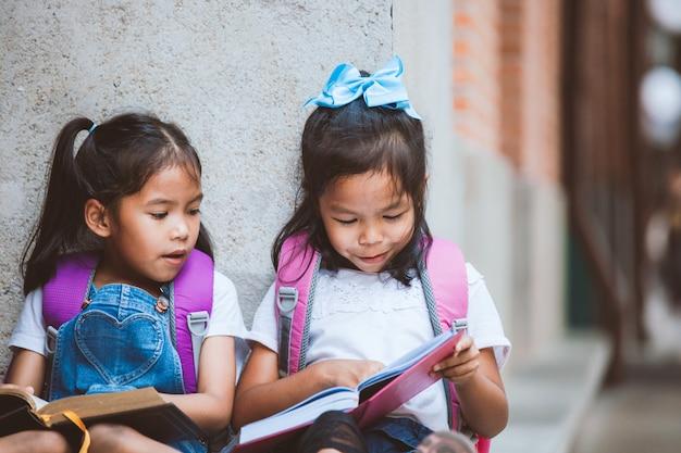 Zwei nette asiatische schülermädchen, die zusammen ein buch in der schule mit spaß und glück lesen