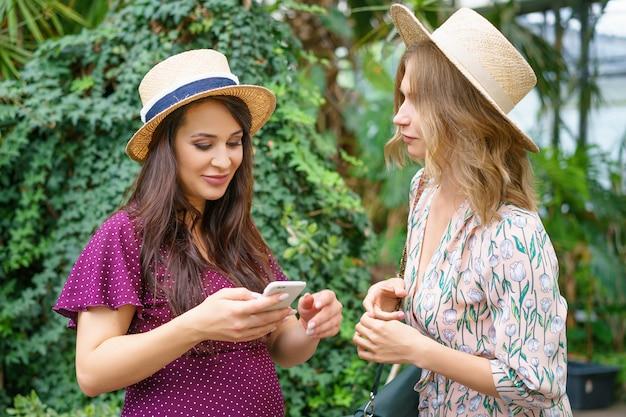 Zwei nette freunde betrachten das telefon, machen selfie hüte auf einem grünen natürlichen hintergrund.