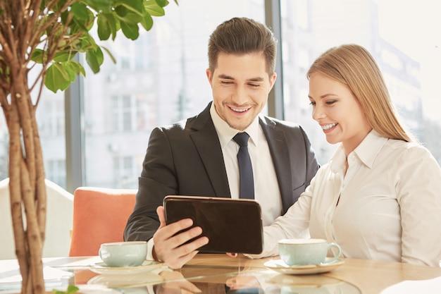 Zwei nette geschäftskollegen, die, genießend lachen, eine digitale tablette an der kaffeestube verwendend