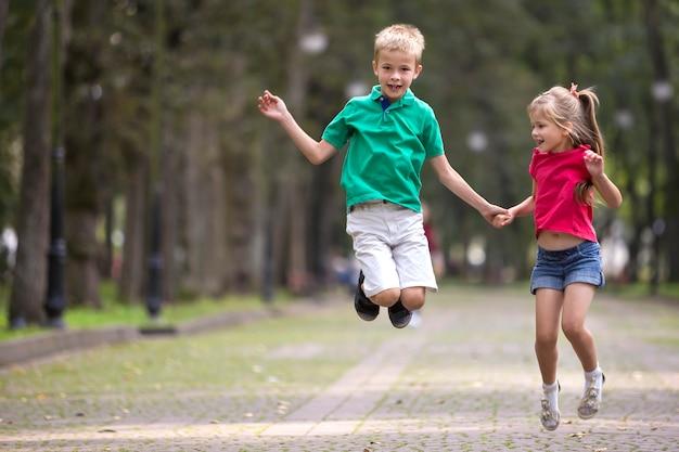 Zwei nette junge lustige lächelnde kinder, mädchen und junge, bruder und schwester, spaß auf unscharfem hellem sonnigem park springend und haben.