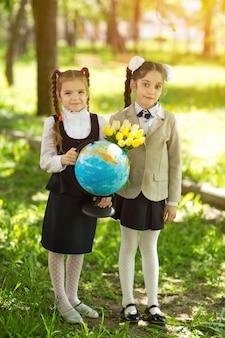 Zwei nette kaukasische mädchenschulmädchen mit blumen und einer kugel