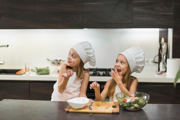 Zwei nette lächelnde geschwister, die spaß in der küche haben