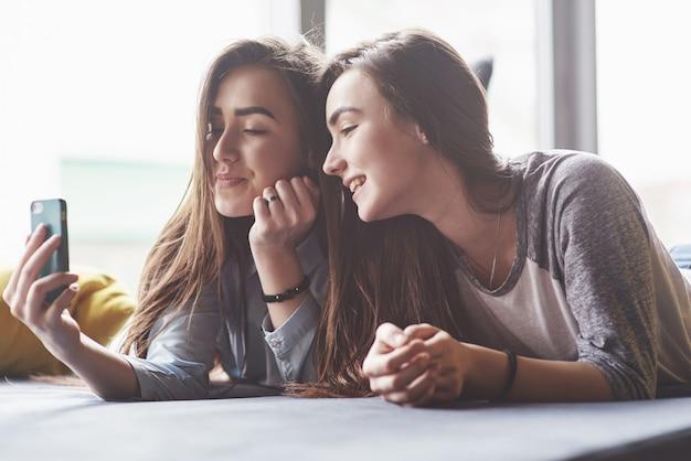 Zwei nette lächelnde zwillingsschwestern, die smartphone halten und selfie machen. mädchen liegen auf der couch und posieren vor freude