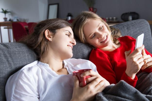 Zwei nette mädchen, die auf couch stillstehen und nettes video genießen