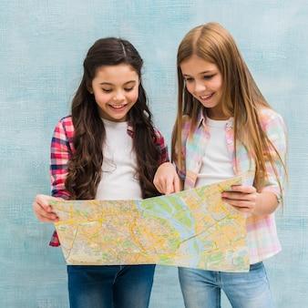 Zwei nette mädchen, die gegen die blaue gemalte wand stehen, die in der karte sucht