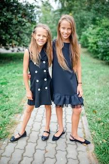 Zwei nette smilling kleine mädchen, die vor ihrer schule aufwerfen.