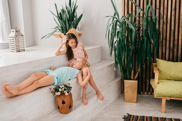Zwei nette weibliche kinder mit dem frohen umarmenden und aufwerfenden gesichtsausdruck