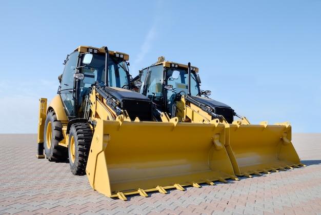 Zwei neue bulldozer auf einem blauen himmelhintergrund