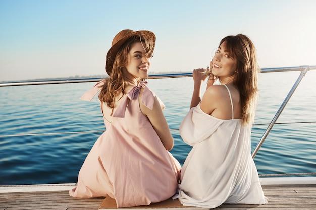 Zwei niedliche europäische freundinnen, die an der seite des bootes sitzen und sich zurückdrehen, um zu schauen, während sie in guter laune breit lächeln.