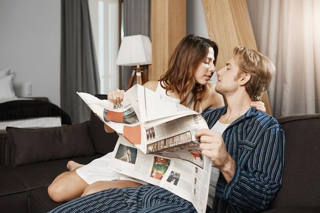 Zwei niedliche europäische leute, die verliebt sind, küssen und umarmen, während sie zu hause auf der couch sitzen und zeitung im pyjama lesen. jungvermählten genießen ihren ersten morgen als ehemann und ehefrau.